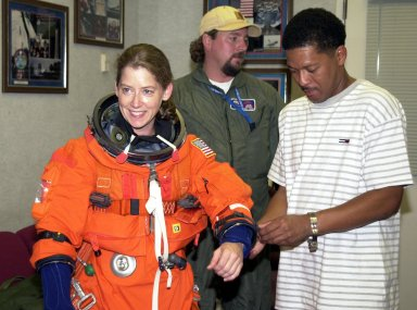KENNEDY SPACE CENTER, FLA. --STS-112 Pilot Pamela Melroy receives some assistance with her spacesuit as she prepares to participate in landing exercises in the Shuttle Training Aircraft at the Shuttle Landing Facility.