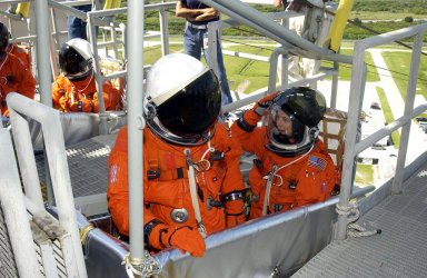 KENNEDY SPACE CENTER, FLA. -- Sitting in a slidewire basket on the 195-foot level of the Fixed Service Structure, Launch Pad 39B, are STS-112 Commander Jeffrey Ashby (left foreground) and Pilot Pamela Melroy. They and the rest of the crew are practicing emergency egress from the pad during Terminal Countdown Demonstration Test activities. Mission STS-112 aboard Space Shuttle Atlantis is scheduled to launch no earlier than Oct. 2, between 2 and 6 p.m. EDT. STS-112 is the 15th assembly mission to the International Space Station. Atlantis will be carrying the S1 Integrated Truss Structure, the first starboard truss segment, to be attached to the central truss segment, S0, and the Crew and Equipment Translation Aid (CETA) Cart A. The CETA is the first of two human-powered carts that will ride along the ISS railway, providing mobile work platforms for future spacewalking astronauts.