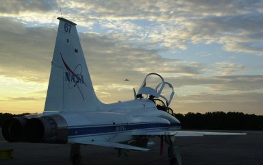 KENNEDY SPACE CENTER, FLA. --Framed by a T-38 on the Shuttle Landing Facility, the Shuttle Training Aircraft can be seen in the distance against the sunset. Commander Jeffrey Ashby and Pilot Pamela Melroy are going through landing exercises on the SLF.