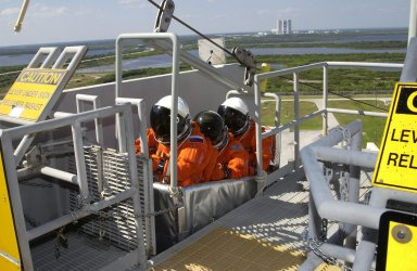 KENNEDY SPACE CENTER, FLA. -- The Expedition 6 crew practice emergency egress from the 195-foot level of the Fixed Service Structure on Launch Pad 39A. In the slidewire basket are (from left) cosmonaut Nikolai Budarin, astronaut Donald Pettit and Commander Ken Bowersox. The crew, travelers on Mission STS-113, will be replacing Expedition 5 on the International Space Station. Along with Expedition 6, STS-113 will carry the Port 1 (P1) truss aboard Space Shuttle Endeavour. Mission STS-113 is scheduled to launch Nov. 10, 2002.