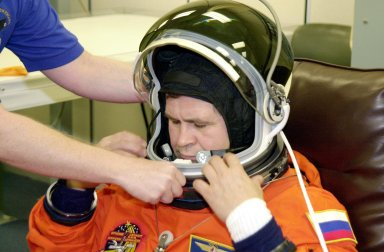 KENNEDY SPACE CENTER, FLA. - Expedition 6 flight engineer Nikolai Budarin gets help with his helmet during suitup for launch on mission STS-113. Budarin, who represents the Russian Space Agency, will be making his second Shuttle flight. The primary mission is bringing the Expedition 6 crew to the Station and returning the Expedition 5 crew to Earth. The major objective of the mission is delivery of the Port 1 (P1) Integrated Truss Assembly, which will be attached to the port side of the S0 truss. Three spacewalks are planned to install and activate the truss and its associated equipment. Launch of Space Shuttle Endeavour on mission STS-113 is scheduled for Nov. 11 at 12:58 a.m. EST.