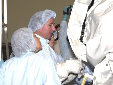 KENNEDY SPACE CENTER, FLA. - At the Space Station Processing Facility, STS-114 Mission Specialist Stephen Robinson (center), dressed in cleanroom attire, participates in familiarization activities on equipment that will fly on the STS-114 mission, as support personnel look on. STS-114 is a utilization and logistics flight that will carry Multi-Purpose Logistics Module Raffaello and the External Stowage Platform (ESP-2), as well as the Expedition 7 crew, to the International Space Station. Launch of STS-114 is currently targeted for March 1, 2003.