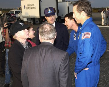 KENNEDY SPACE CENTER, FLA. - Mrs. Daniel R. Mulville shakes hands with Kent V. Rominger, Deputy Director of Flight Crew Operations, on the runway of the Shuttle Landing Facility following the landing of Endeavour. Mrs. Mulville is the wife of Dr. Daniel R. Mulville, NASA Associate Deputy Administrator. In the group, from left are KSC Director Roy D. Bridges; Mrs. Mulville; Dr. Mulville (back to camera); James D. Halsell Jr., Manager of Launch Integration at KSC, Space Shuttle Program; Rominger; and STS-113 Commander James Wetherbee. Commander Wetherbee earlier guided Space Shuttle Endeavour to a flawless touchdown on runway 33 at the Shuttle Landing Facility after completing the 13-day, 18-hour, 48-minute, 5.74-million mile STS-113 mission to the International Space Station. Main gear touchdown was at 2:37:12 p.m. EST, nose gear touchdown was at 2:37:23 p.m., and wheel stop was at 2:38:25 p.m. Poor weather conditions thwarted landing opportunities until a fourth day, the first time in Shuttle program history that a landing has been waved off for three consecutive days. The orbiter also carried the other members of the STS-113 crew, Pilot Paul Lockhart and Mission Specialists Michael Lopez-Alegria and John Herrington, as well as the returning Expedition Five crew, Commander Valeri Korzun, ISS Science Officer Peggy Whitson and Flight Engineer Sergei Treschev. The installation of the P1 truss on the International Space Station was accomplished during the mission.