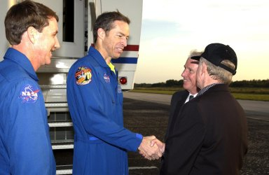 KENNEDY SPACE CENTER, FLA. - STS-113 Commander James Wetherbee shakes hands with KSC Director Roy D. Bridges Jr. following landing at the Shuttle Landing Facility. From left are Kent Rominger, Deputy Director of Flight Crew Operations, Wetherbee, Dr. Daniel R. Mulville, NASA Associate Deputy Administrator, and Bridges. Commander Wetherbee earlier guided Space Shuttle Endeavour to a flawless touchdown on runway 33 at the Shuttle Landing Facility after completing the 13-day, 18-hour, 48-minute, 5.74-million mile STS-113 mission to the International Space Station. Main gear touchdown was at 2:37:12 p.m. EST, nose gear touchdown was at 2:37:23 p.m., and wheel stop was at 2:38:25 p.m. Poor weather conditions thwarted landing opportunities until a fourth day, the first time in Shuttle program history that a landing has been waved off for three consecutive days. The orbiter also carried the other members of the STS-113 crew, Pilot Paul Lockhart and Mission Specialists Michael Lopez-Alegria and John Herrington, as well as the returning Expedition Five crew, Commander Valeri Korzun, ISS Science Officer Peggy Whitson and Flight Engineer Sergei Treschev. The installation of the P1 truss on the International Space Station was accomplished during the mission.