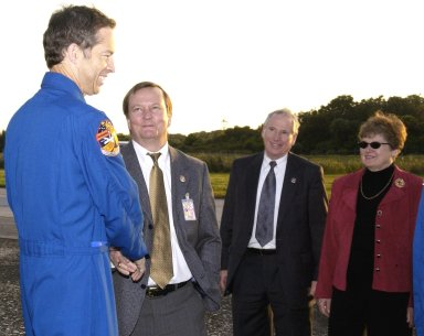 KENNEDY SPACE CENTER, FLA. - STS-113 Commander James Wetherbee shakes hands with Michael D. Leinbach, Shuttle Launch Director at KSC, on the runway of the Shuttle Landing Facility following the landing of Endeavour. From left are Wetherbee, Leinbach, Dr. Daniel R. Mulville, NASA Associate Deputy Administrator, and Mrs. Mulville. Commander Wetherbee earlier guided Space Shuttle Endeavour to a flawless touchdown on runway 33 at the Shuttle Landing Facility after completing the 13-day, 18-hour, 48-minute, 5.74-million mile STS-113 mission to the International Space Station. Main gear touchdown was at 2:37:12 p.m. EST, nose gear touchdown was at 2:37:23 p.m., and wheel stop was at 2:38:25 p.m. Poor weather conditions thwarted landing opportunities until a fourth day, the first time in Shuttle program history that a landing has been waved off for three consecutive days. The orbiter also carried the other members of the STS-113 crew, Pilot Paul Lockhart and Mission Specialists Michael Lopez-Alegria and John Herrington, as well as the returning Expedition Five crew, Commander Valeri Korzun, ISS Science Officer Peggy Whitson and Flight Engineer Sergei Treschev. The installation of the P1 truss on the International Space Station was accomplished during the mission.