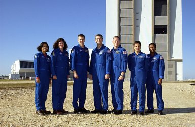 """KENNEDY SPACE CENTER, FLA. -- The STS-107 crew poses for a group portrait with the Vehicle Assembly Building in the background. They are at KSC to take part in Terminal Countdown Demonstration Test activities, a standard part of launch preparations. From left to right are Mission Specialists Kalpana Chawla and Laurel Clark, Pilot William """"Willie"""" McCool, Commander Rick Husband, Mission Specialist David Brown, Payload Specialist Ilan Ramon (the first Israeli astronaut), and Payload Commander Michael Anderson. STS-107 is a mission devoted to research and will include more than 80 experiments that will study Earth and space science, advanced technology development, and astronaut health and safety. Launch is targeted for Jan. 16, 2003, between 10 a.m. and 2 p.m. EST."""