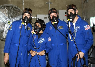 """KENNEDY SPACE CENTER, FLA. -- During emergency egress training, part of Terminal Countdown Demonstration Test activities at the pad, STS-107 crew members test breathing masks in the emergency bunker. From left are Pilot William """"Willie"""" McCool, Mission Specialists Kalpana Chawla and David Brown, and Commander Rick Husband. STS-107 is a mission devoted to research and will include more than 80 experiments that will study Earth and space science, advanced technology development, and astronaut health and safety. Launch is planned for Jan. 16, 2003, between 10 a.m. and 2 p.m. EST aboard Space Shuttle Columbia. ."""