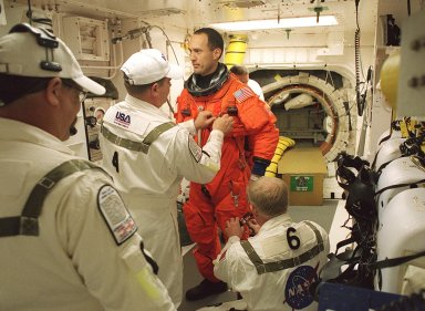 KENNEDY SPACE CENTER, FLA. - In the White Room, STS-109 Mission Specialist James H. Newman is helped with his launch and entry suit by Rene Arriens (left), USA mechanical technician, and Danny Wyatt, NASA quality assurance specialist (right, kneeling). Behind Newman is the opened hatch of Space Shuttle Columbia. On the mission, Columbia will rendezvous with the Hubble Space Telescope for the crew to replace and upgrade key telescope systems through five challenging spacewalks. After an extensive 2-1/2 year modification period during which many systems were replaced and enhanced, Columbia is making its 27th flight in the Shuttle program. After the 11-day mission, Columbia is expected to land at Kennedy Space Center March 12