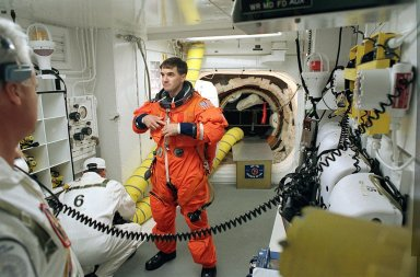 """KENNEDY SPACE CENTER, FLA. - A member of the Closeout Crew helps STS-110 Mission Specialist Rex J. Walheim with his launch and entry suit before he enters Space Shuttle Atlantis. The White Room provides entry into the cockpit area of the orbiter. This is Walheim's first Shuttle flight. STS-110 is carrying the S0 Integrated Truss Structure and Mobile Transporter (MT) on this 13th assembly flight to the International Space Station. On the 11-day mission, astronauts, including Walheim, will make four spacewalks to attach the S0 truss, which will become the backbone of the Space Station, to the U.S. Lab, """"Destiny."""" The MT, a space """"railcar,"""" is attached to the truss segment and will make its debut run during the flight. Launch is scheduled for 4:40 p.m. EDT (20:40 GMT)"""