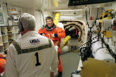 """KENNEDY SPACE CENTER, FLA. - STS-110 Pilot Stephen Frick jokes with the Closeout Crew in the White Room as he makes final preparations to enter Space Shuttle Atlantis for launch. The White Room provides entry into the cockpit area of the orbiter. This is Frick's first Shuttle flight. STS-110 is carrying the S0 Integrated Truss Structure and Mobile Transporter (MT) on this 13th assembly flight to the International Space Station. On the 11-day mission, astronauts will make four spacewalks to attach the S0 truss, which will become the backbone of the Space Station, to the U.S. Lab, """"Destiny."""" The MT, a space """"railcar,"""" is attached to the truss segment and will make its debut run during the flight. Launch is scheduled for 4:40 p.m. EDT (20:40 GMT)"""