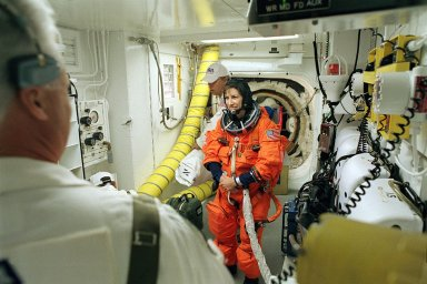 """KENNEDY SPACE CENTER, FLA. -- STS-110 Mission Specialist Ellen Ochoa has final suit preparations - In the White Room before entering Space Shuttle Atlantis for launch. The White Room provides entry into the cockpit area of the orbiter. This is Ochoa's fourth Shuttle flight. On this 13th assembly flight to the International Space Station, STS-110 is carrying the S0 Integrated Truss Structure and Mobile Transporter (MT). During the 11-day mission, astronauts will make four spacewalks to attach the S0 truss, which will become the backbone of the Space Station, to the U.S. Lab, """"Destiny."""" The MT, a space """"railcar,"""" is attached to the truss segment and will make its debut run during the flight. Launch is scheduled for 4:40 p.m. EDT (20:40 GMT)."""