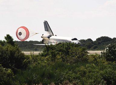 KENNEDY SPACE CENTER, FLA. - A drag chute slows Atlantis after touchdown on Runway 33 at the Shuttle Landing Facility, completing the 4.5-million-mile journey to the International Space Station. Main gear touchdown occurred at 11:43:40 a.m. EDT; nose gear touchdown at 11:43:48 a.m.; and wheel stop at 11:44:35 a.m. Mission elapsed time was 10:19:58:44. Mission STS-112 expanded the size of the Station with the addition of the S1 truss segment. The returning crew of Atlantis are Commander Jeffrey Ashby, Pilot Pamela Melroy, and Mission Specialists David Wolf, Piers Sellers, Sandra Magnus and Fyodor Yurchikhin. This landing is the 60th at KSC in the history of the Shuttle program.