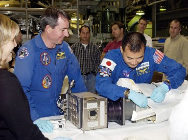 KENNEDY SPACE CENTER, FLA. -- STS-114 Mission Specialist Soichi Noguchi (right), with the National Space Development Agency of Japan (NASDA), works with equipment as Mission Specialist Stephen K. Robinson, Ph.D., (left) watches. The STS-114 crew is participating in familiarization activities with the hardware that will fly on the mission. STS-114 is a utilization and logistics flight (ULF-1) that will carry Multi-Purpose Logistics Module Raffaello and the External Stowage Platform (ESP-2), as well as the Expedition 7 crew, to the International Space Station. Launch is targeted for March 1, 2003.
