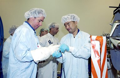 KENNEDY SPACE CENTER, FLA. - At the SPACEHAB facility in Cape Canaveral, STS-114 Mission Specialist Stephen K. Robinson, Ph.D., (left foreground) gets help with a glove from Mission Specialist Soichi Noguchi (right), of the National Space Development Agency of Japan (NASDA). They are participating in familiarization activities with the hardware that will fly on the STS-114 mission. STS-114 is a utilization and logistics flight that will carry Multi-Purpose Logistics Module Raffaello and the External Stowage Platform (ESP-2), as well as the Expedition 7 crew, to the International Space Station. Launch is targeted for March 1, 2003.
