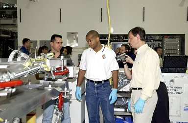 KENNEDY SPACE CENTER, FLA. - In the Space Station Processing Facility, STS-116 Pilot William Oefelein (left), Mission Specialists Robert Curbeam (center) and Christer Fuglesang (right) check out equipment for the mission during a Crew Equipment Interface Test activity. Fuglesang is with the European Space Agency. Mission STS-116 is the 19th assembly flight to the International Space Station, delivering the third port truss segment, the P5 Truss, that will be attached to the second port truss segment, the P3/P4 Truss. The mission will also deliver the eighth expedition crew to the ISS and return Expedition 7. STS-116 is scheduled for launch July 24, 2003.