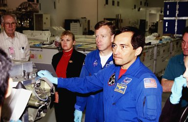 KENNEDY SPACE CENTER, FLA. - During a Crew Equipment Interface Test activity, STS-119 Commander Steven Lindsey (center) and Mission Specialist Carlos Noriega (right) listen to instructions on the equipment that will be part of the mission. Scheduled to launch in January 2004, the mission will deliver the fourth and final set of U.S. solar arrays along with the fourth starboard truss segment, the S6 truss.