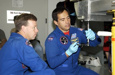 KENNEDY SPACE CENTER, FLA. - During a Crew Equipment Interface Test activity, STS-119 Commander Steven Lindsey watches as Mission Specialist Carlos Noriega works with a tool on the equipment that will be part of the mission. Scheduled to launch in January 2004, the mission will deliver the fourth and final set of U.S. solar arrays along with the fourth starboard truss segment, the S6 truss.