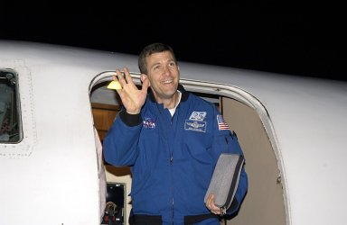 """KENNEDY SPACE CENTER, FLA. - STS-107 Commander Rick Husband waves to spectators as he arrives at KSC for pre-launch preparations. STS-107 is a mission devoted to research and will include more than 80 experiments that will study Earth and space science, advanced technology development, and astronaut health and safety. The payload on Space Shuttle Columbia includes FREESTAR (Fast Reaction Experiments Enabling Science, Technology, Applications and Research) and the SHI Research Double Module (SHI/RDM), known as SPACEHAB. Experiments on the module range from material sciences to life sciences. The crew includes Payload Specialist Ilan Ramon, the first Israeli astronaut. Other crew members are Pilot William """"Willie"""" McCool, Payload Commander Michael Anderson and Mission Specialists Kalpana Chawla, David Brown and Laurel Clark. Launch of Columbia is targeted for Jan. 16 between 10 a.m. and 2 p.m."""