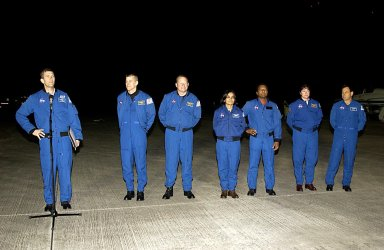 """KENNEDY SPACE CENTER, FLA. -STS-107 Commander Rick Husband (at the microphone) makes a few comments after the crew's arrival at KSC for pre-launch preparations. Standing left to right are Husband, Pilot William """"Willie"""" McCool, Mission Specialists David Brown and Kalpana Chawla, Payload Commander Michael Anderson, Mission Specialist Laurel Clark and Payload Specialist Ilan Ramon, who is the first Israeli astronaut to fly on a Shuttle mission. STS-107 is a mission devoted to research and will include more than 80 experiments that will study Earth and space science, advanced technology development, and astronaut health and safety. The payload on Space Shuttle Columbia includes FREESTAR (Fast Reaction Experiments Enabling Science, Technology, Applications and Research) and the SHI Research Double Module (SHI/RDM), known as SPACEHAB. Experiments on the module range from material sciences to life sciences. Launch of Columbia is targeted for Jan. 16 between 10 a.m. and 2 p.m."""