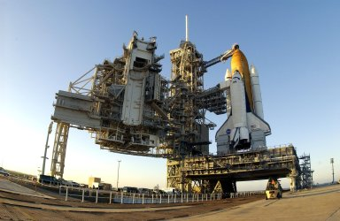 """KENNEDY SPACE CENTER, FLA. -- After rollback of the Rotating Service Structure on Launch Pad 39A, Space Shuttle Columbia is revealed atop its Mobile Launch Platform. Visible is the gaseous oxygen vent arm and cap, called the """"beanie cap"""", extended above the orange external tank. Columbia is scheduled for launch Jan. 16 at 10:39 a.m. EST on mission STS-107, a research mission."""