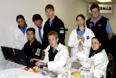 KENNEDY SPACE CENTER, FLA. - Students pause during their work on their experiments that will fly in SPACEHAB on Space Shuttle Columbia on mission STS-107. SPACEHAB's complement of commercial experiments includes six educational experiments designed and developed by students in six different countries under the auspices of Space Technology and Research Students (STARS), a global education program managed by SPACEHAB subsidiary Space Media. The countries represented are Australia, China, Israel, Japan, Liechtenstein and the United States. The student investigators who conceived these experiments will monitor their operations in space. The experiments will be housed in BioServe Space Technologies' Isothermal Containment Module (ICM --a small temperature-controlled facility that provides experiment support such as physical containment, lighting, and video imaging) and stowed in a middeck-size locker aboard the SPACEHAB Research Double Module.