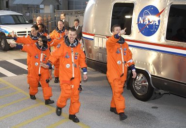"""KENNEDY SPACE CENTER, FLA. - The STS-107 crew heads for the Astrovan and a ride to Launch Pad 39A for liftoff. In front, left to right, are Payload Specialist Ilan Ramon, Mission Specialist Kalpana Chawla and Pilot William """"Willie"""" McCool; behind them, left to right, are Payload Commander Michael Anderson, Mission Specialists David Brown and Laurel Clark, and Mission Commander Rick Husband. Ramon is the first astronaut from Israel to fly on a Shuttle. The 16-day mission is devoted to research and will include more than 80 experiments that will study Earth and space science, advanced technology development, and astronaut health and safety. The payload on Space Shuttle Columbia includes FREESTAR (Fast Reaction Experiments Enabling Science, Technology, Applications and Research) and the SHI Research Double Module (SHI/RDM), known as SPACEHAB. Experiments on the module range from material sciences to life sciences. Liftoff is scheduled for 10:39 a.m. EST."""