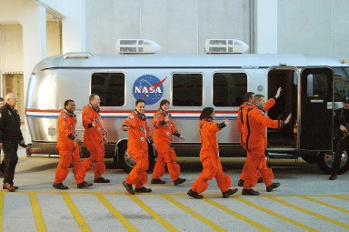 """KENNEDY SPACE CENTER, FLA. -- The STS-107 crew heads for the Astrovan and a ride to Launch Pad 39A for liftoff. From left to right are Payload Commander Michael Anderson, Mission Specialist David Brown, Payload Specialist Ilan Ramon, Mission Specialists Laurel Clark and Kalpana Chawla, Mission Commandaer Rick Husband and Pilot William """"Willie"""" McCool. Ramon is the first astronaut from Israel to fly on a Shuttle. The 16-day mission is devoted to research and will include more than 80 experiments that will study Earth and space science, advanced technology development, and astronaut health and safety. The payload on Space Shuttle Columbia includes FREESTAR (Fast Reaction Experiments Enabling Science, Technology, Applications and Research) and the SHI Research Double Module (SHI/RDM), known as SPACEHAB. Experiments on the module range from material sciences to life sciences. Liftoff is scheduled for 10:39 a.m. EST. [Photo courtesy of Scott Andrews]"""