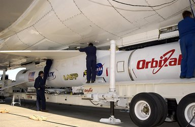 KENNEDY SPACE CENTER, FLA. - Technicians on Cape Canaveral Air Force Station, Fla., work to attach the Pegasus XL launch vehicle and Solar Radiation and Climate Experiment (SORCE) to the L-1011 aircraft. The L-1011 will carry the Pegasus to the launch altitude of 39,000 feet over the Atlantic Ocean approximately 100 miles east-southeast of Cape Canaveral. SORCE, built by Orbital Sciences Corporation, will study and measure solar irradiance as a source of energy in the Earth's atmosphere. The launch of SORCE is scheduled for Jan. 25 at 3:14 p.m. from CCAFS.