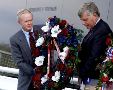 KENNEDY SPACE CENTER, FLA. - Following the tragic loss of Columbia and crew on their return to Earth, Center Director Roy Bridges and Deputy Director James Kennedy place a wreath in front of the Astronauts Memorial Space Mirror at the KSC Visitor Complex. The mirror is a national tribute to the earlier 17 American astronauts who also gave their lives to the quest to explore space. The site has been inundated with flowers from the public to honor the fallen crew of Columbia.