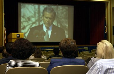 KENNEDY SPACE CENTER, FLA. - Employees at KSC watch President George Bush on NASA television as he speaks at the memorial service for the fallen seven astronauts of Columbia bieng held at Johnson Space Center, Houston. .