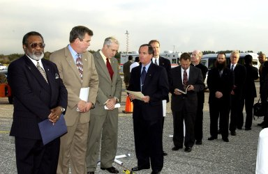 KENNEDY SPACE CENTER, FLA. - A Columbia Crew Memorial Service is held at the Shuttle Landing Facility for KSC employees and invited guests, including (from left) NASA Associate Deputy Administrator for Institutions and Asset Management James L. Jennings, Florida Gov. Jeb Bush, NASA Administrator Sean O'Keefe, and Columbia's first pilot and former KSC Director Robert Crippen. The Columbia and her crew of seven were lost on Feb. 1, 2003, over East Texas as they returned to Earth after a 16-day research mission. Taking part in the service were NASA Administrator Sean O?Keefe, former KSC Director Robert Crippen, astronaut Jim Halsell, several employees, area clergymen, and members of Patrick Air Force Base. The service concluded with a ?Missing Man Formation Fly Over? by NASA T-38 jet aircraft.