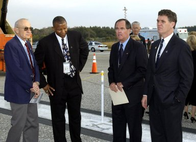 KENNEDY SPACE CENTER, FLA. - A Columbia Crew Memorial Service is held at the Shuttle Landing Facility for KSC employees and invited guests, including former KSC Director of Shuttle Processing Robert Sieck (left), KSC lead vehicle manager Kelvin Manning (next), and Columbia's first pilot and former KSC Director Robert Crippen (third from left). The Columbia and her crew of seven were lost on Feb. 1, 2003, over East Texas as they returned to Earth after a 16-day research mission. Taking part in the service were NASA Administrator Sean O?Keefe, former KSC Director Robert Crippen, astronaut Jim Halsell, several employees, area clergymen, and members of Patrick Air Force Base. The service concluded with a ?Missing Man Formation Fly Over? by NASA T-38 jet aircraft.