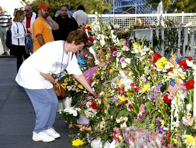 KENNEDY SPACE CENTER, FLA. -- Near the Astronauts Memorial Space Mirror at the KSC Visitor Complex, guests leave flowers as a tribute to the fallen crew of Columbia. The Columbia and her crew of seven were lost on Feb. 1, 2003, over East Texas as they returned to Earth after a 16-day research mission, STS-107.