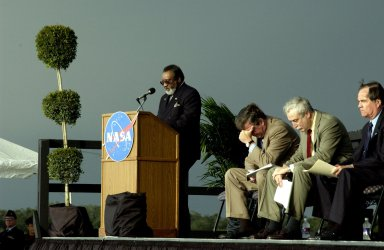 KENNEDY SPACE CENTER, FLA. - A Columbia Crew Memorial Service is held at the Shuttle Landing Facility for KSC employees and invited guests. NASA Associate Deputy Administrator for Institutions and Asset Management James L. Jennings is at the podium. The Columbia and her crew of seven were lost on Feb. 1, 2003, over East Texas as they returned to Earth after a 16-day research mission. Taking part in the service were NASA Administrator Sean O?Keefe, former KSC Director Robert Crippen, astronaut Jim Halsell, several employees, area clergymen, and members of Patrick Air Force Base. The service concluded with a ?Missing Man Formation Fly Over? by NASA T-38 jet aircraft.