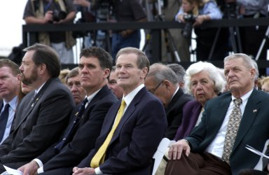 KENNEDY SPACE CENTER, FLA. - A Columbia Crew Memorial Service is held at the Shuttle Landing Facility for KSC employees and invited guests. Florida Senator Bill Nelson, seated in the center (gold tie), flew on Columbia in 1986 as a payload specialist on mission STS 61-C. Beside him (left) is Congressman Dave Weldon. The Columbia and her crew of seven were lost on Feb. 1, 2003, over East Texas as they returned to Earth after a 16-day research mission. Taking part in the service were NASA Administrator Sean O?Keefe, former KSC Director Robert Crippen, astronaut Jim Halsell, several employees, area clergymen, and members of Patrick Air Force Base. The service concluded with a ?Missing Man Formation Fly Over? by NASA T-38 jet aircraft.