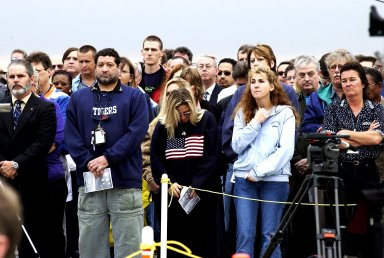 KENNEDY SPACE CENTER, FLA. -- Employees at KSC give solemn attention to the memorial service for the Columbia crew held at the Shuttle Landing Facility. The crew were lost on Feb. 1, 2003, over East Texas as they returned to Earth after the 16-day research mission STS-107. Taking part in the service were NASA Administrator Sean O'Keefe, former KSC Director Robert Crippen, astronaut Jim Halsell, several employees, area clergymen, and members of Patrick Air Force Base. Crippen was the first to fly Columbia in 1981; Halsell first flew Columbia in 1994 and again in 1997.