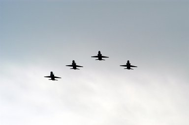 """KENNEDY SPACE CENTER, FLA. -- NASA T-38 jet aircraft are flying in a """"Missing Man Formation"""" to conclude the memorial service for the crew of Columbia who were lost on Feb. 1, 2003, over East Texas as they returned to Earth after a 16-day research mission STS-107. The service was held at the Shuttle Landing Facility. Taking part in the service were NASA Administrator Sean O'Keefe, former KSC Director Robert Crippen, astronaut Jim Halsell, several employees, area clergymen, and members of Patrick Air Force Base. Crippen was the first to fly Columbia in 1981; Halsell first flew Columbia in 1994 and again in 1997."""