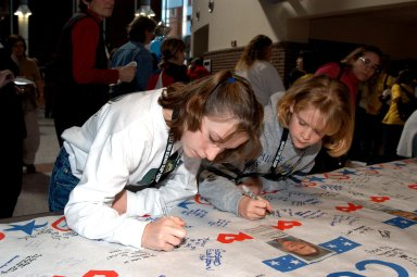 KENNEDY SPACE CENTER, FLA. -- At the Sally Ride Science Festival, held at the University of Central Florida, Orlando, Fla., young women gather to sign a large poster in tribute to the Columbia astronauts who were lost in the Shuttle's explosion the day before. The Sally Ride event promotes science, math and technology as future career paths for girls. Former astronaut Sally Ride addressed the girls, while breakout sessions afforded closer interaction between Ride and festival attendees.