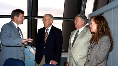"""KENNEDY SPACE CENTER, FLA. - At the KSC Launch Control Complex, former astronauts Jim Lovell (second from left) and Wally Schirra (second from right) talk with Mike Wetmore, director of Shuttle Processing (far left). At far right is Lisa Malone, acting deputy director of External Relations & Business Development at KSC. Lovell and Schirra visited KSC to talk about the space program and their experiences, as well as offer encouragement to workers to help get the space program """"back on its feet."""" They visited several sites around the Center, including the RLV Hangar where Columbia debris is being collected and examined as part of the investigation into the tragedy that claimed the orbiter and lives of seven astronauts returning from mission STS-107."""
