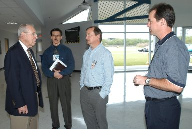 """KENNEDY SPACE CENTER, FLA. - During a visit to KSC, former astronaut Jim Lovell (far left) talks to (from right) Space Shuttle Test Director Steve Altemus, Launch Director Mike Leinbach, and reconstruction engineer John Cowart. Lovell, along with former astronaut Wally Schirra, visited KSC to talk about the space program and their experiences, as well as offer encouragement to workers to help get the space program """"back on its feet."""" They visited several sites around the Center, including the RLV Hangar where Columbia debris is being collected and examined as part of the investigation into the tragedy that claimed the orbiter and lives of seven astronauts returning from mission STS-107."""