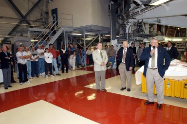 """KENNEDY SPACE CENTER, FLA. - In the Orbiter Processing Facility, Bill Pickavance, vice president and deputy program manager, United Space Alliance, talks to employees. With him, at left, are former astronauts Wally Schirra and Jim Lovell. The latter two visited several KSC sites, relating their experiences in the space program and offerking encouragement to workers to help get the space program """"back on its feet."""" They visited several sites around the Center, including the RLV Hangar where Columbia debris is being collected and examined as part of the investigation into the tragedy that claimed the orbiter and lives of seven astronauts returning from mission STS-107."""