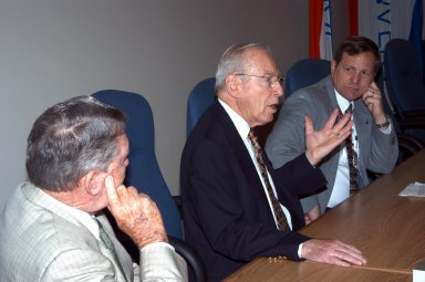 """KENNEDY SPACE CENTER, FLA. - Former astronauts Jim Lovell (center) and Wally Schirra (left) talk with Mike Wetmore, director of Shuttle Processing (right) and others during a visit to KSC. Lovell and Schirra visited KSC to talk about the space program and their experiences, as well as offer encouragement to workers to help get the space program """"back on its feet."""" They visited several sites around the Center, including the RLV Hangar where Columbia debris is being collected and examined as part of the investigation into the tragedy that claimed the orbiter and lives of seven astronauts returning from mission STS-107."""