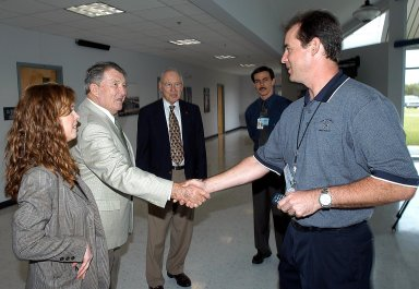 """KENNEDY SPACE CENTER, FLA. - During a visit to KSC, former astronauts Wally Schirra (second from left) and Jim Lovell (third from left) greet Space Shuttle Test Director Steve Altemus. At far left is is Lisa Malone, acting deputy director of External Relations & Business Development at KSC, and reconstruction engineer John Cowart (second from right). Lovell and Schirra visited KSC to talk about the space program and their experiences, as well as offer encouragement to workers to help get the space program """"back on its feet."""" They visited several sites around the Center, including the RLV Hangar where Columbia debris is being collected and examined as part of the investigation into the tragedy that claimed the orbiter and lives of seven astronauts returning from mission STS-107."""