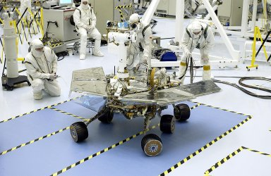 KENNEDY SPACE CENTER, Fla. - Workers in the Payload Hazardous Servicing Facility watch as the Mars Exploration Rover-2 (MER-2) turns. MER-2 is being tested for mobility and maneuverability. Atop the rover, on the left, can be seen the cameras, mounted on a Pancam Mast Assembly (PMA). On the right are the low-gain and high-gain antennas. Set to launch in Spring 2003, the MER Mission will consist of two identical rovers designed to cover roughly 110 yards each Martian day. Each rover will carry five scientific instruments that will allow it to search for evidence of liquid water that may have been present in the planet's past. The rovers will be identical to each other, but will land at different regions of Mars. The first rover has a launch window opening May 30, and the second rover a window opening June 25.