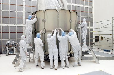 KENNEDY SPACE CENTER, FLA. - Workers adjust a second layer of the payload canister around the Space Infrared Telescope Facility (SIRTF) in the background. SIRTF is currently scheduled for transportation to Launch Complex 17-B, Cape Canaveral Air Force Station, and mating with the Delta II on or about April 4.