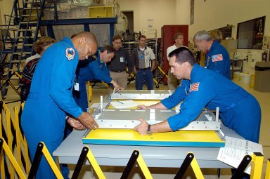 KENNEDY SPACE CENTER, FLA. -- Members of the STS-116 crew handle equipment at SPACEHAB in Port Canaveral, Fla. On the left are Mission Specialists Robert Curbeam and Christer Fuglesang; on the right are Pilot William Oefelein (front) and Commander Terrence Wilcutt. Objective of their mission to the International Space Station is to deliver and attach the third port truss segment, the P5 Truss, deactivate and retract the P6 Truss Channel 4B (port-side) solar array, and reconfigure station power from 2A and 4A solar arrays. A launch date is under review.