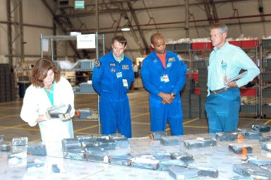 KENNEDY SPACE CENTER, FLA. -- In the RLV Hangar, two members of the STS-116 crew look at pieces of tile from Columbia. Center left is Mission Specialist Christer Fuglesang, with the European Space Agency, and center right is Mission Specialist Robert Curbeam. The Columbia Reconstruction Project Team is examining and identifying pieces as they are delivered to the hangar. More than 70,000 items, weighing 78,000 pounds, about 36 percent of the Shuttle by weight, have been delivered to KSC for use in the mishap investigation.