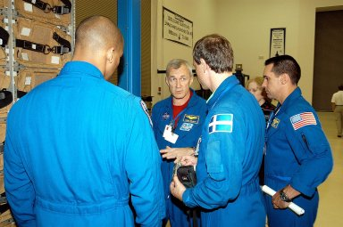 KENNEDY SPACE CENTER, FLA. - The STS-116 crew share thoughts during training at SPACEHAB in Port Canaveral, Fla. From left are Mission Specialist Robert Curbeam, Commander Terrence Wilcutt, Mission Specialist Christer Fuglesang and Pilot William Oefelein. Objective of their mission to the International Space Station is to deliver and attach the third port truss segment, the P5 Truss, deactivate and retract the P6 Truss Channel 4B (port-side) solar array, and reconfigure station power from 2A and 4A solar arrays. A launch date is under review.