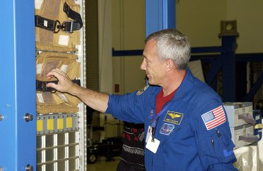 KENNEDY SPACE CENTER, FLA. - STS-116 Commander Terrence Wilcutt reaches for a packet placed inside equipment at SPACEHAB, Port Canaveral, Fla. He and other crew members - Pilot William Oefelein and Mission Specialists Robert Curbeam and Christer Fuglesang - are training at the facility. Objective of their mission to the International Space Station is to deliver and attach the third port truss segment, the P5 Truss, deactivate and retract the P6 Truss Channel 4B (port-side) solar array, and reconfigure station power from 2A and 4A solar arrays. A launch date is under review.