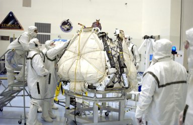 KENNEDY SPACE CENTER, FLA. - Kevin Burke, with the Jet Propulsion Laboratory in Pasadena, Calif., checks the closure of the lander petals and rover egress hardware around the Mars Exploration Rover 2 (MER-A). Visible now are the airbags that will inflate to cushion the landing on Mars. The lander and rover will subsequently be enclosed within an aeroshell for launch. The MER Mission consists of two identical rovers designed to cover roughly 110 yards each Martian day over various terrain. Each rover will carry five scientific instruments that will allow it to search for evidence of liquid water that may have been present in the planet's past. Identical to each other, the rovers will land at different regions of Mars. Launch date for this first of NASA's two Mars Exploration Rover missions is scheduled no earlier than June 6.